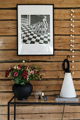 Black-and-white photo on rustic board wall above modern console table