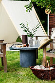 Grey table and wooden chairs in front of play tent in summery garden