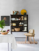 Baskets, crockery and ornaments in dark display cabinet against white wall