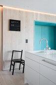 Pale wood and blue seating niche in modern, minimalist kitchen