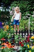Mädchen gießt Blumen im eingezäunten Mini-Garten