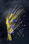 Barley and cornflowers arranged on dark surface