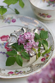 Lilac blossoms and rose petals in a silver egg cup