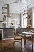 Designerstühle am Esstisch vor der offenen Küche im Landhausstil