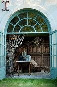 Blick durch geöffnete Flügeltüren in Pavillon mit antikem Gartenzubehör