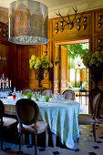 Flower arrangements, wood-panelled walls and hunting trophies in stylish dining room