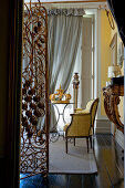 Ornate metal screen and antique armchair in stylish yellow parlour
