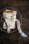 Bundle of letters tied with lace ribbon on glass plate with gilt edge