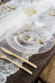 Table set with glass plates, golden cutlery and lace tablecloth