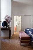 Elegant bedroom bench at foot of bed in bedroom with ensuite bathroom