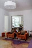 Two orange velvet armchairs in front of open doorway leading into kitchen-dining room