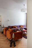 Orange armchairs and purple sofa in living room