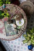 Verschiedene Dekoobjekte auf rundem Vintage-Balkontisch