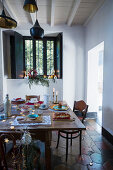 Festively set table in simple, rustic interior