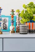 Photo, candlesticks, candle lantern and houseplant on grey sideboard