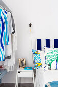 Bed with blue-and-white striped headboard, bedside table and clothes rail