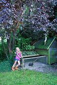 Little girl next to rabbit run in garden