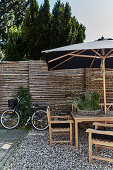 Shallow wicker basket planted with herbs in seating area with parasol on gravel terrace