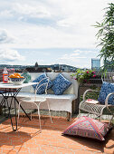 Table, bench, chairs and floor cushion on roof terrace