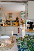 Candles on table and view into open-plan country-house-style kitchen