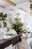 Set table and Christmas tree in open-plan interior