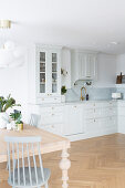 Kitchen-dining room in Scandinavian country-house style with pale grey cabinets