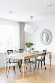 Grey and black spoke-back chairs around table with turned legs
