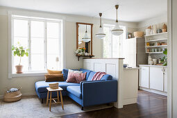 Blue sofa against partition wall screening open-plan kitchen