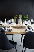 Candles, glass and wooden baubles on festively set wooden table