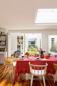 Dining table with red tablecloth below skylight in open-plan dining area