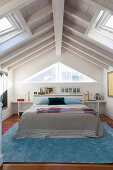 Double bed in attic room with wooden ceiling