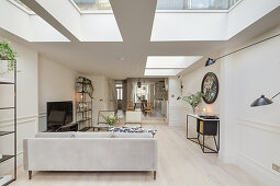 Open-plan, elongated, white interior with skylights