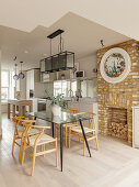 Glass dining table and brick fireplace in open-plan kitchen