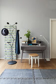 Grey writing desk next to decorative wall panel and designer coat stand