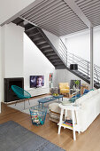 Sofa, easy chairs and TV in seating area below steel staircase in loft apartment