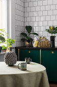 Table in kitchen with dark green cupboards and exotic accessories