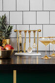 Golden cocktail utensils hung on stand in kitchen