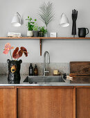 Flamingo flowers in bear-shaped vase next to sink in simple kitchen