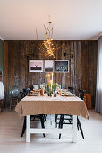 Set table below chandelier made from branches in dining area with board wall