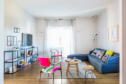 Metal shelves, fifties chairs and blue sofa in light-flooded living room