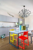 Simple grey kitchen counter, dining table and designer chairs in various colours