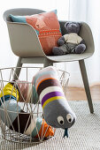 Fabric snake in metal basket next to grey shell chair in child's bedroom