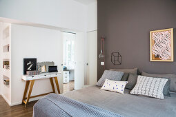 Grey double bed against taupe partition wall screening walk-in wardrobe