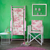 Folding chair with toile-de-jouy fabric seat and back in front of green wall