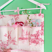 Hand-sewn organiser made from toile-de-jouy fabric hanging from clothes hanger