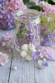 Hydrangea flowers, lady's mantle and plaster flower around preserving jar