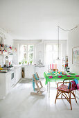 White kitchen-dining room with white floor and brightly coloured accents