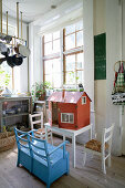Blue bench in front of dolls' house in country-house-style kitchen-dining room