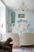 Chandelier above antique bed in vintage-style bedroom