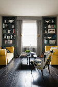Two yellow sofas facing one another in symmetrical living room in shades of grey